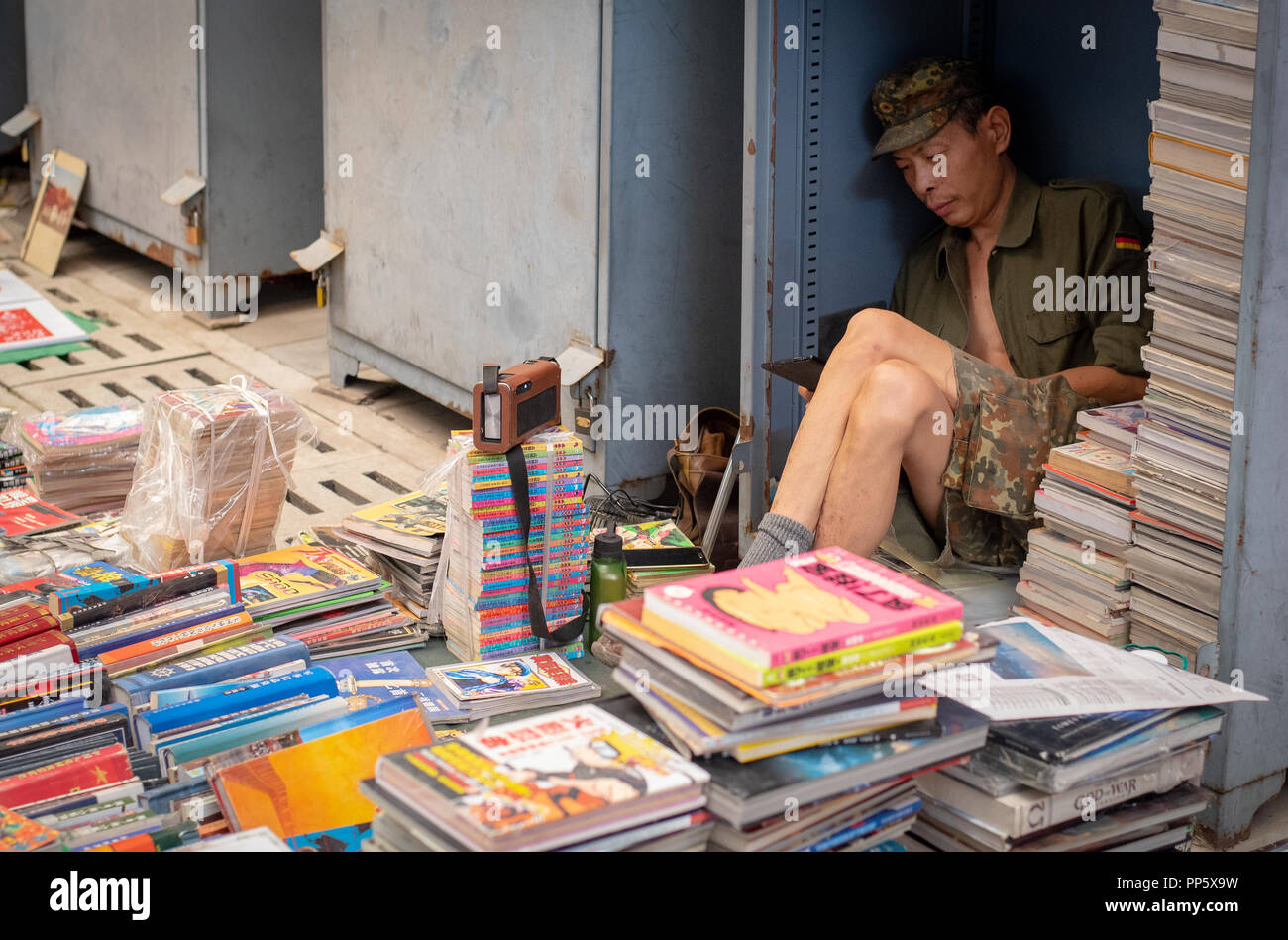 Chinese man working as a Book seller selling books and waiting for customer at an open book market in Beijing city, Chin - Stock Image