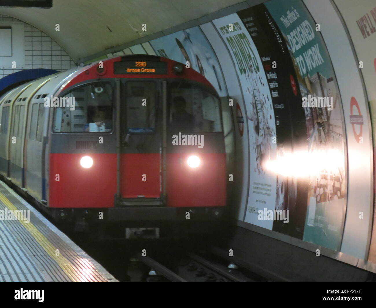 A London tube train arrives at Leicester Square on the Piccadilly Line, heading towards its final destination, Arnos Grove. - Stock Image