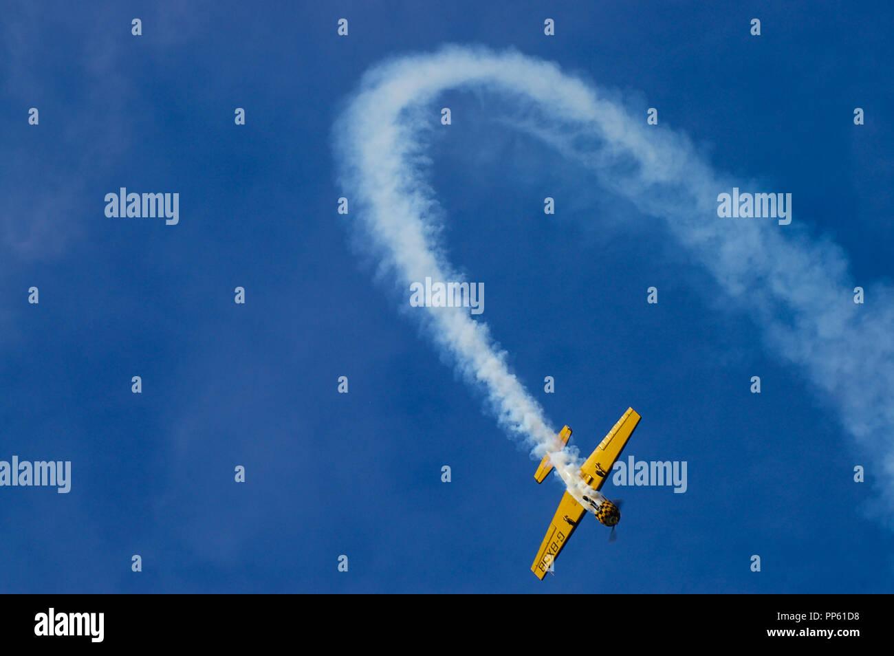 Yakovlev Yak-52 aerobatic plane arcing over with smoke trail in blue sky. Flying aerobatics. Loop the loop. Looping. Space for copy - Stock Image