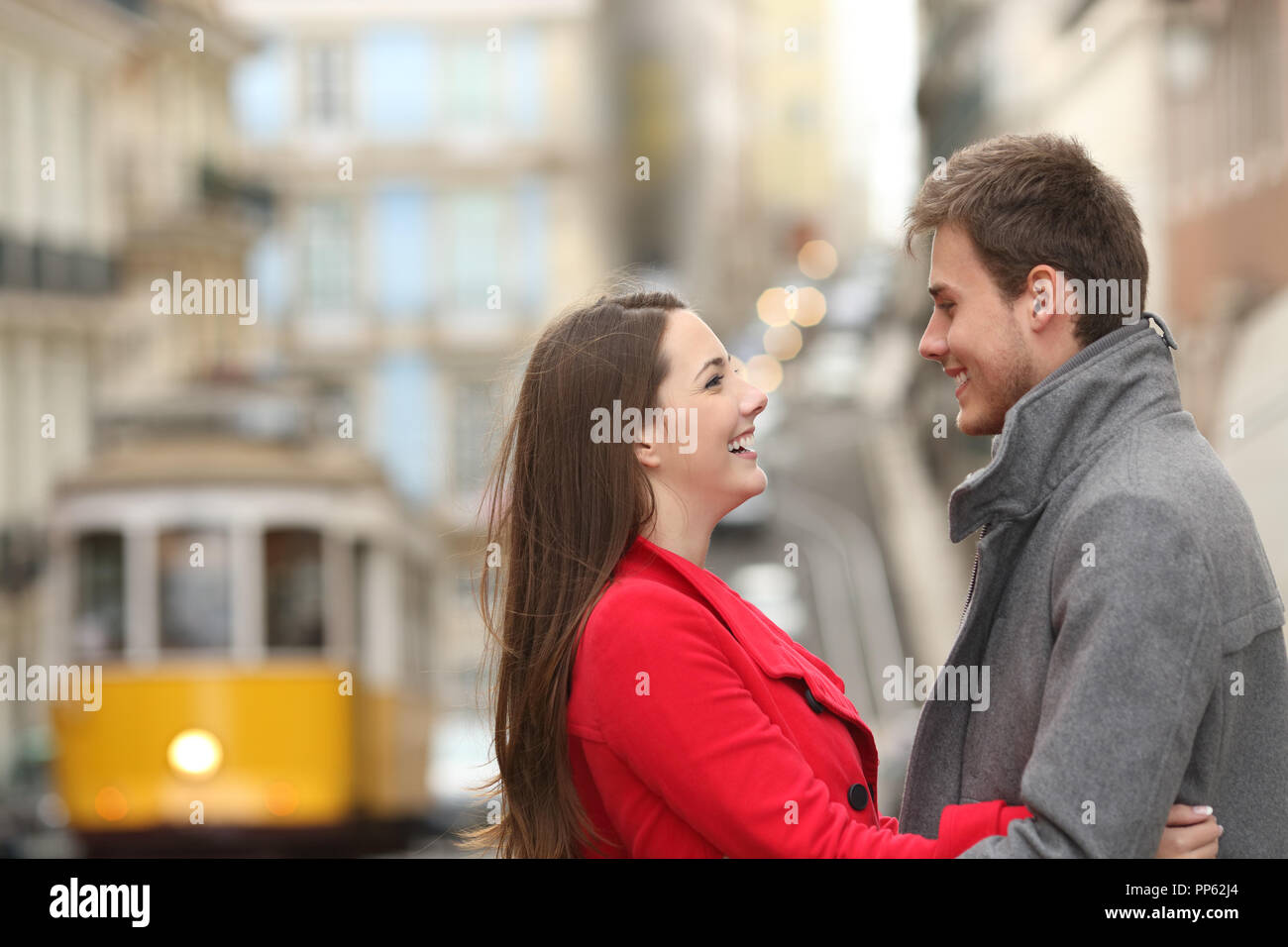 Side view portrait of a cheerful couple looking each other in the street Stock Photo