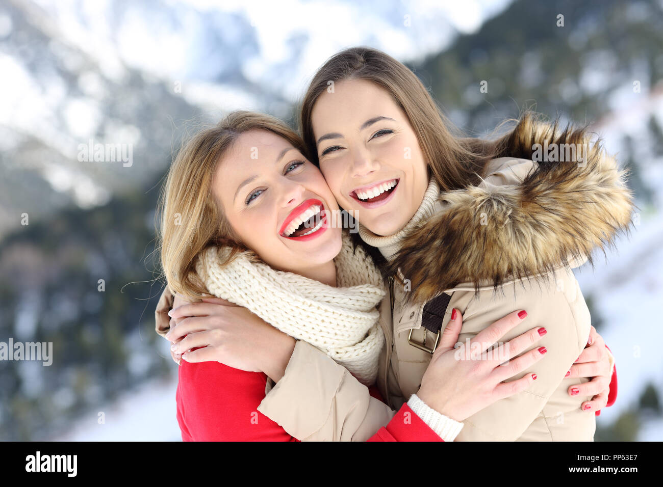 Happy friends cuddling and posing in winter holiday in a snowy mountain Stock Photo