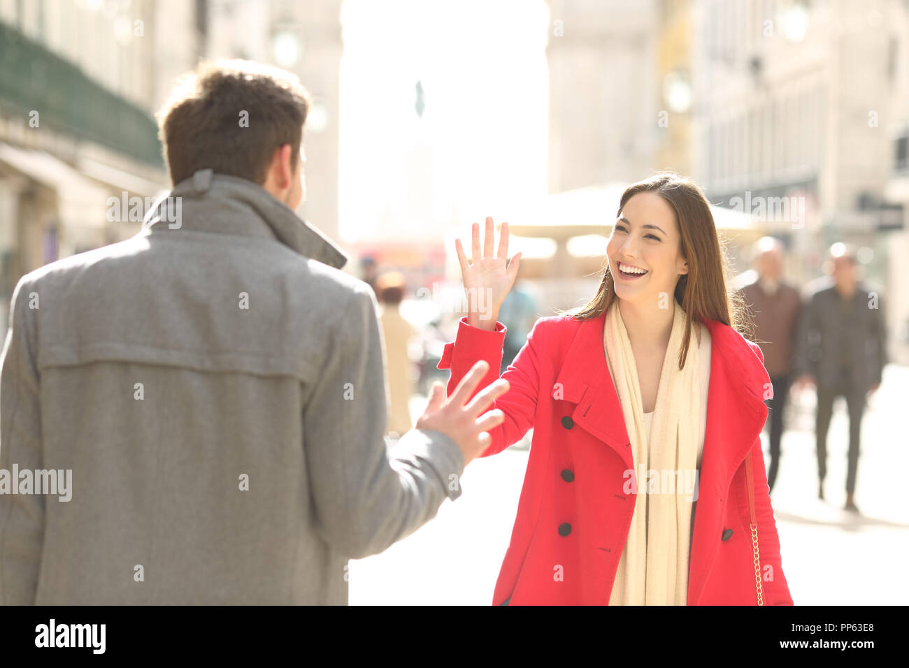 Two happy friends meeting and greeting in the street of a big city - Stock Image