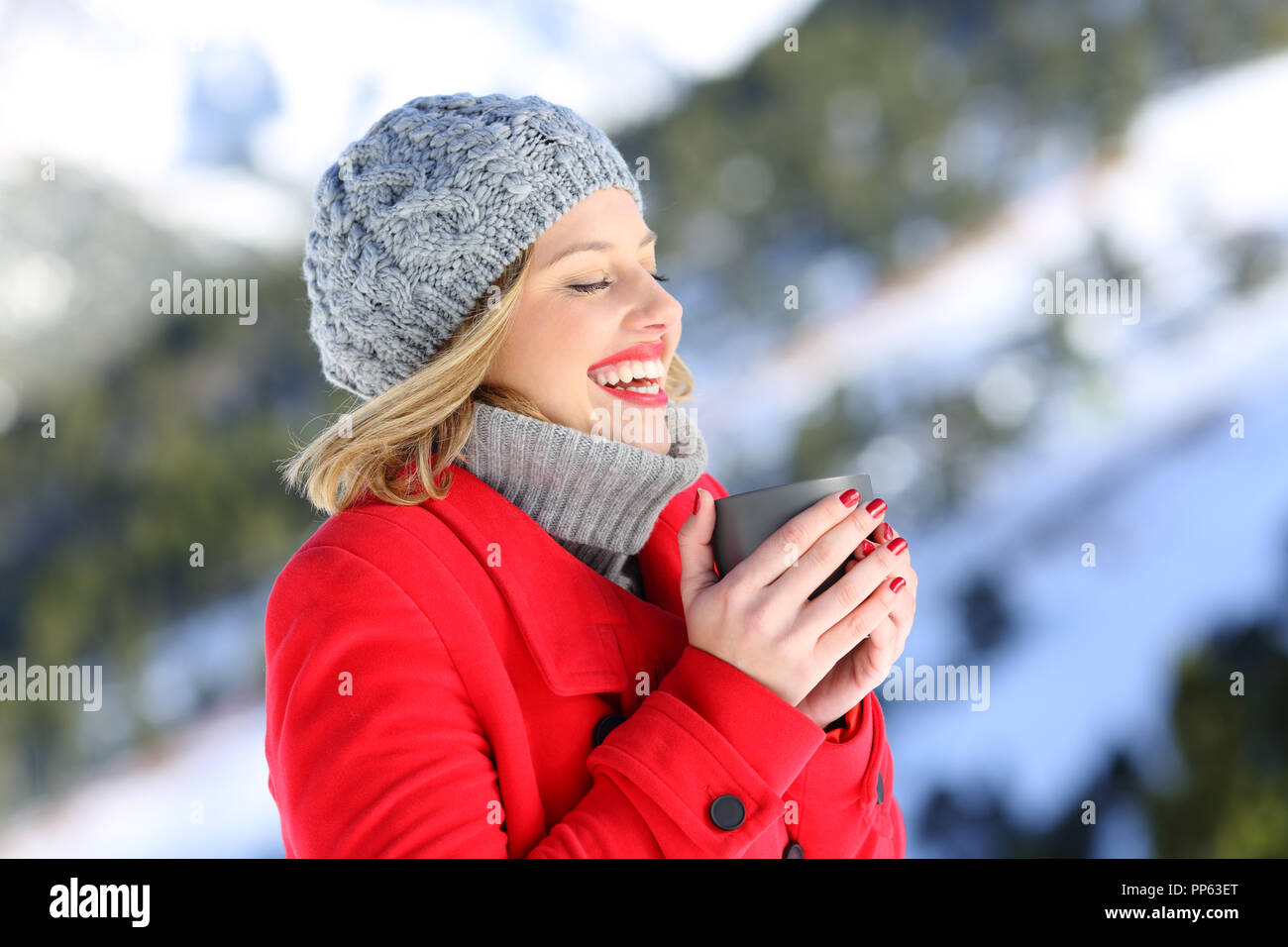 75a31de92574 Happy woman keeping warm holding a coffee mug in a snowy mountain in ...