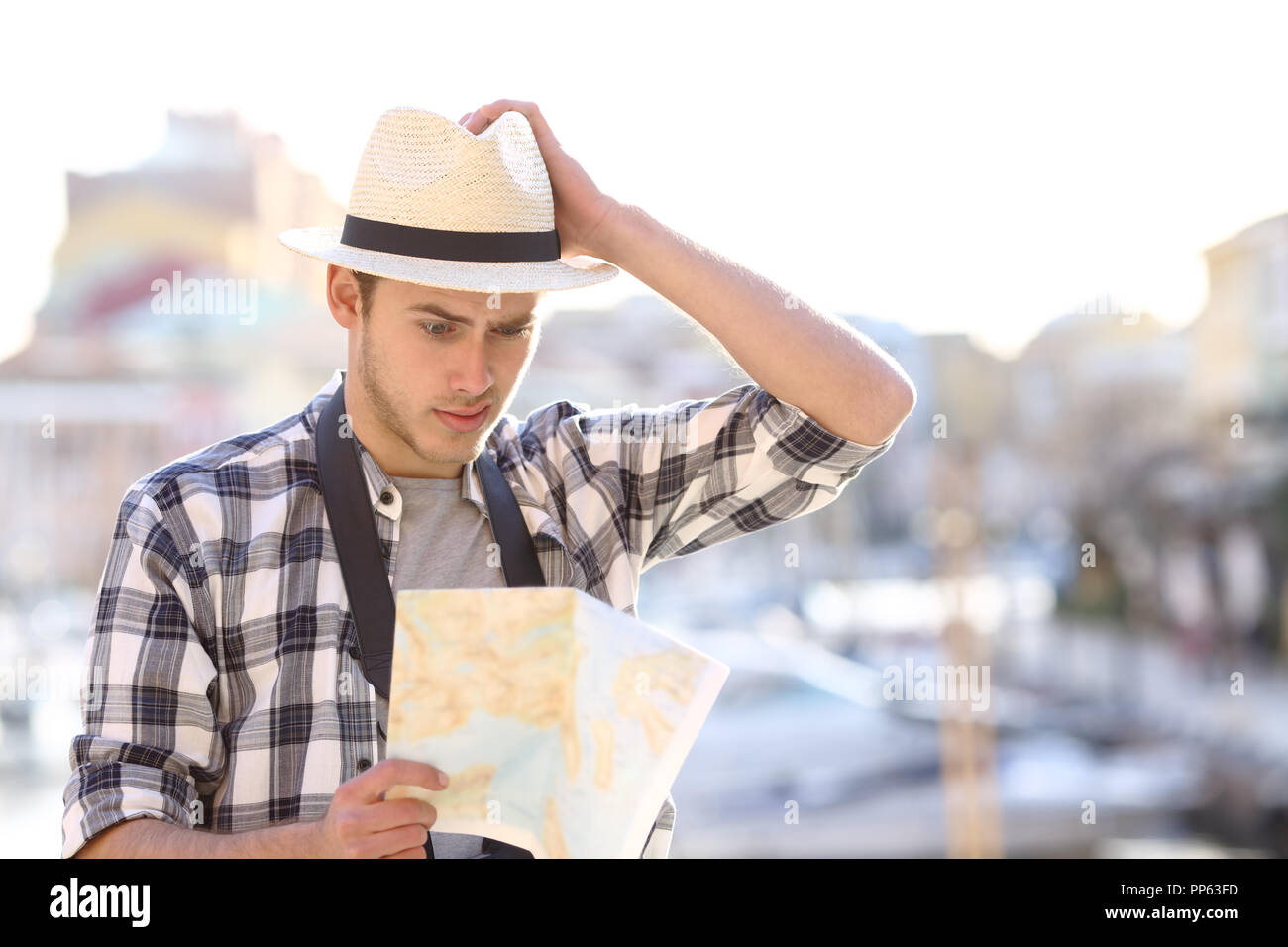 Lost tourist consulting a confusing guide in a coast town street on vacation - Stock Image