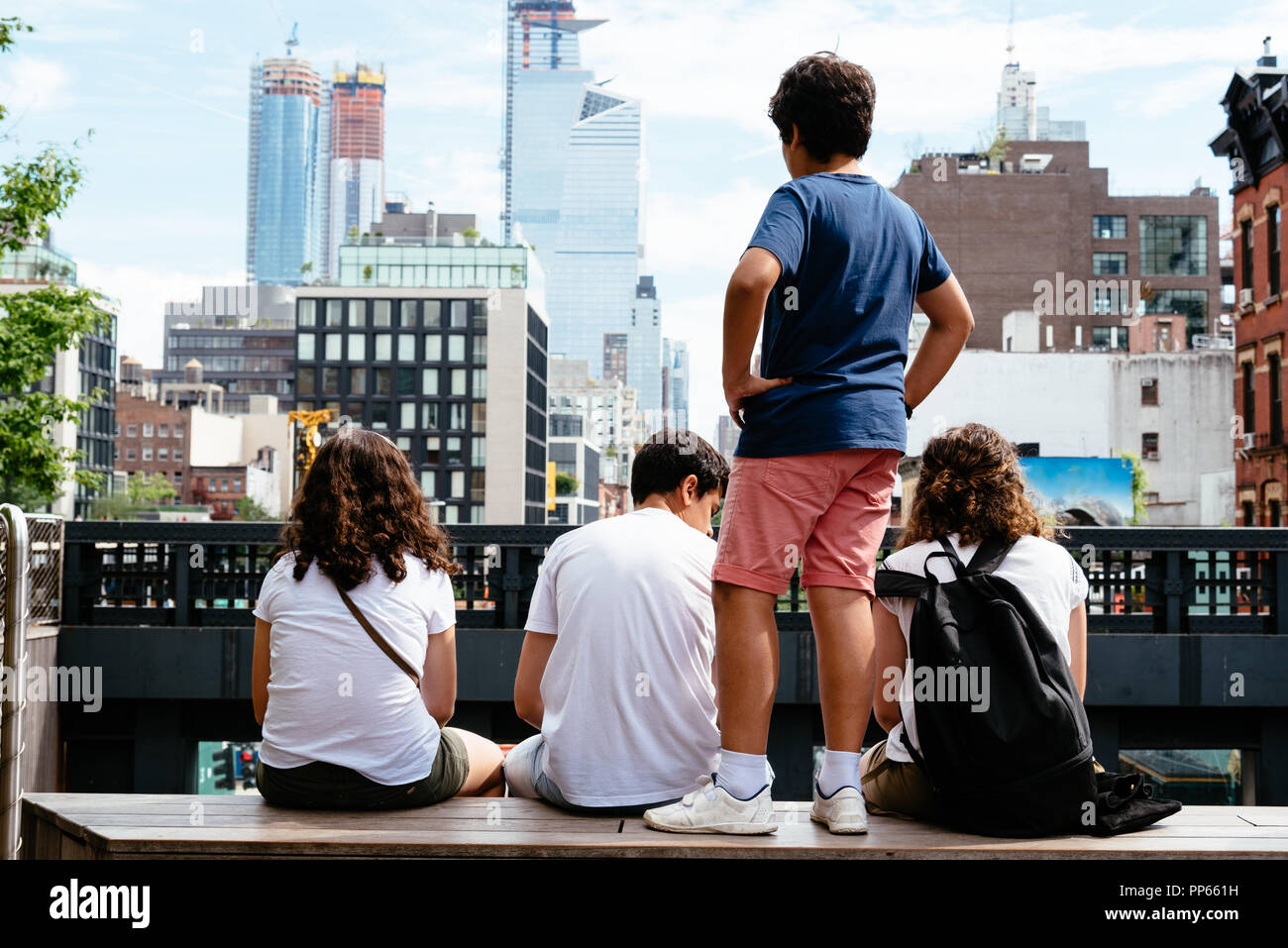 Four young people sitting in Observatory point in High Line against skyline of New York City - Stock Image