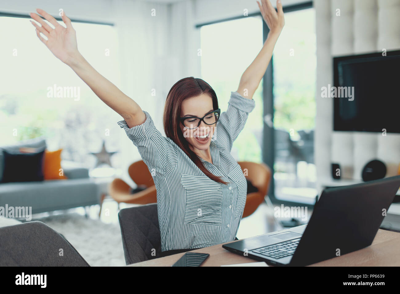 Happy modern nerd woman win at laptop indoors, success and happiness, arms raised - Stock Image