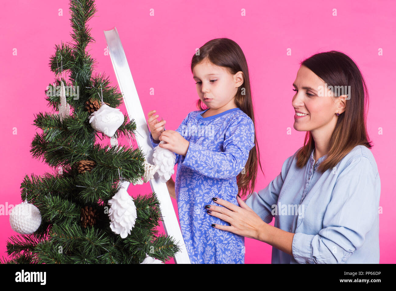 christmas childhood and people concept child girl standing on step ladder decorating the christmas tree with her mother on pink background