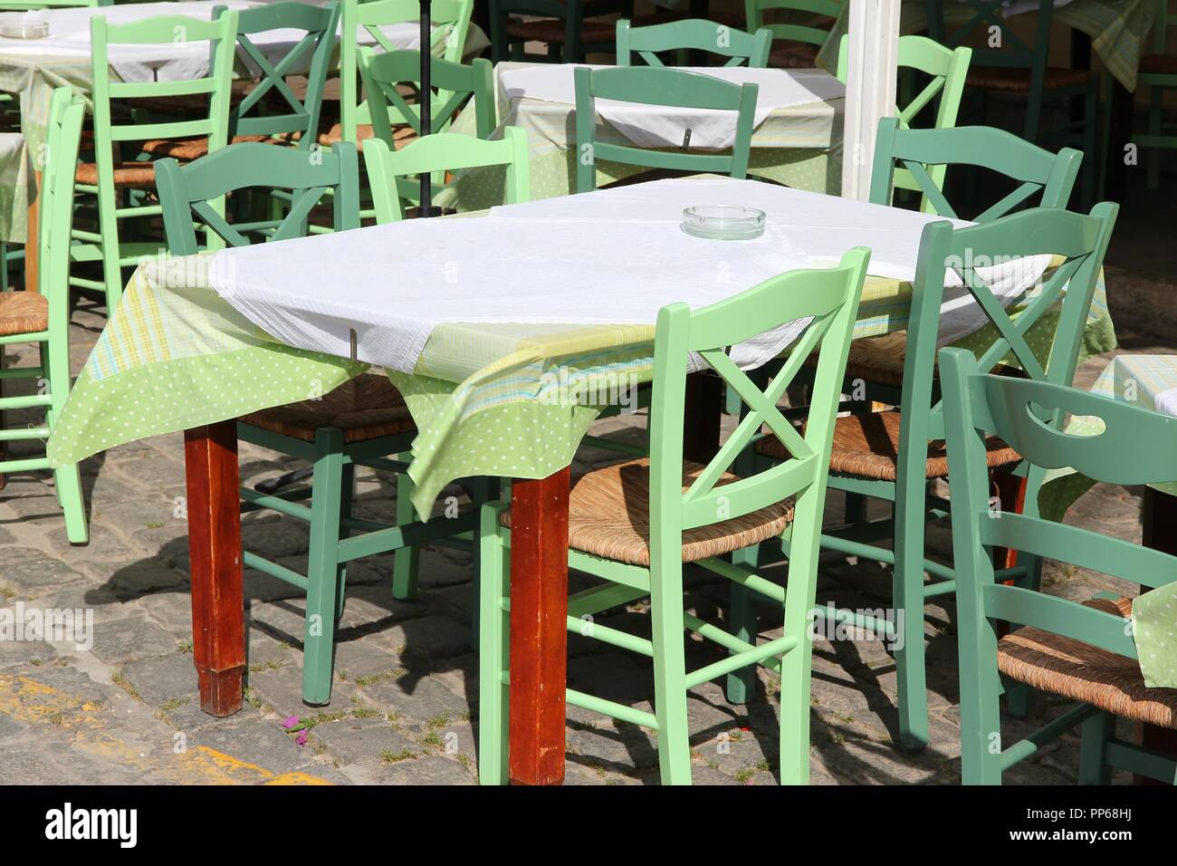 Restaurant tables and green chairs in athens greece