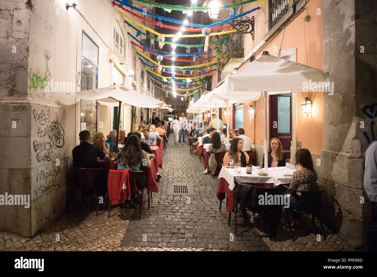 Alfama district Lisbon, people have a dinner in tipical restaurant in the street. - Stock Image