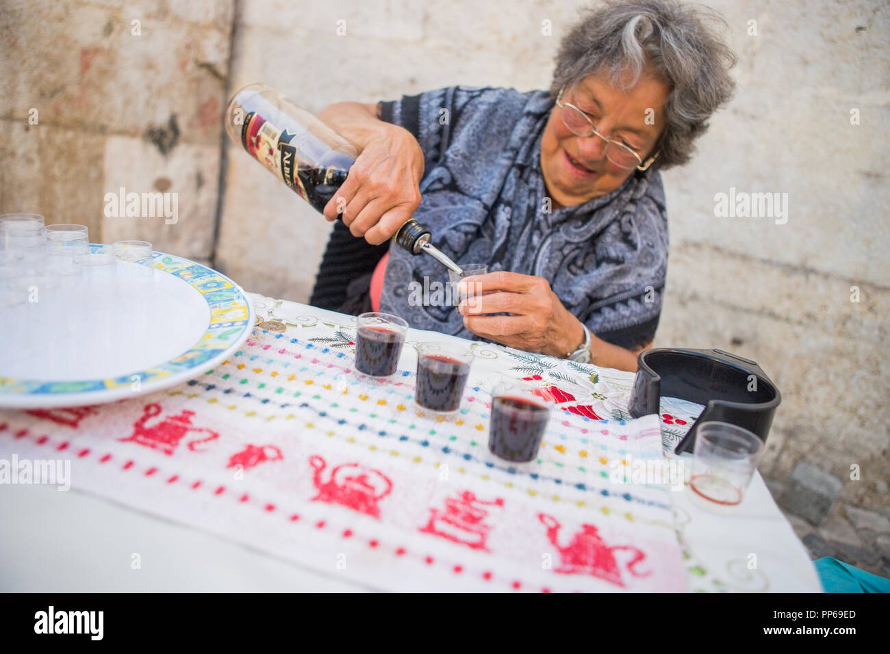 Lisbon, Alfama district, Portugal old woman sell a tast of tipical Ginja liqueur Ginjinha jinjinha cherry alcoho - Stock Image