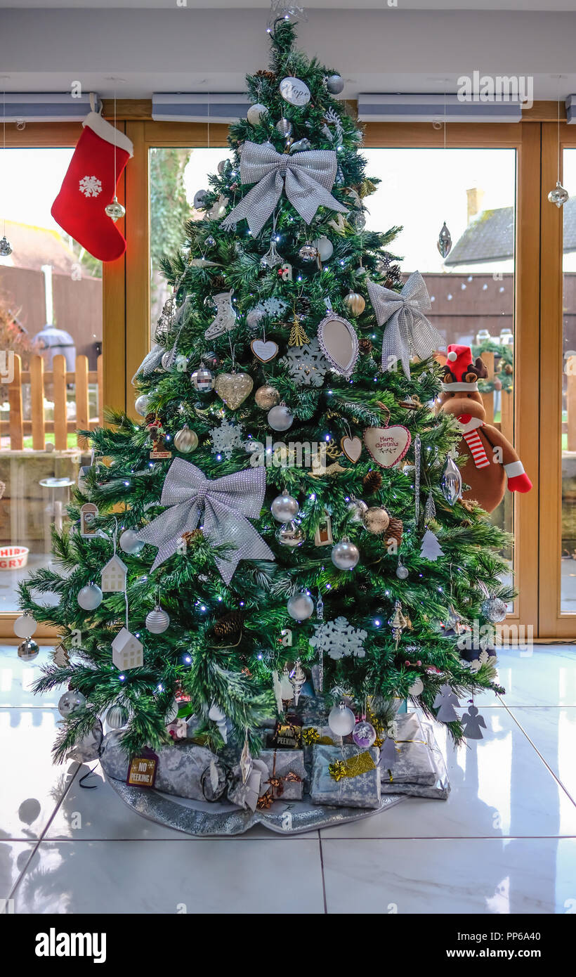 essex england uk december 15 2017christmas tree with silver trim set in a living room lots of decorations and present left underneath - Silver Christmas Decorations Uk