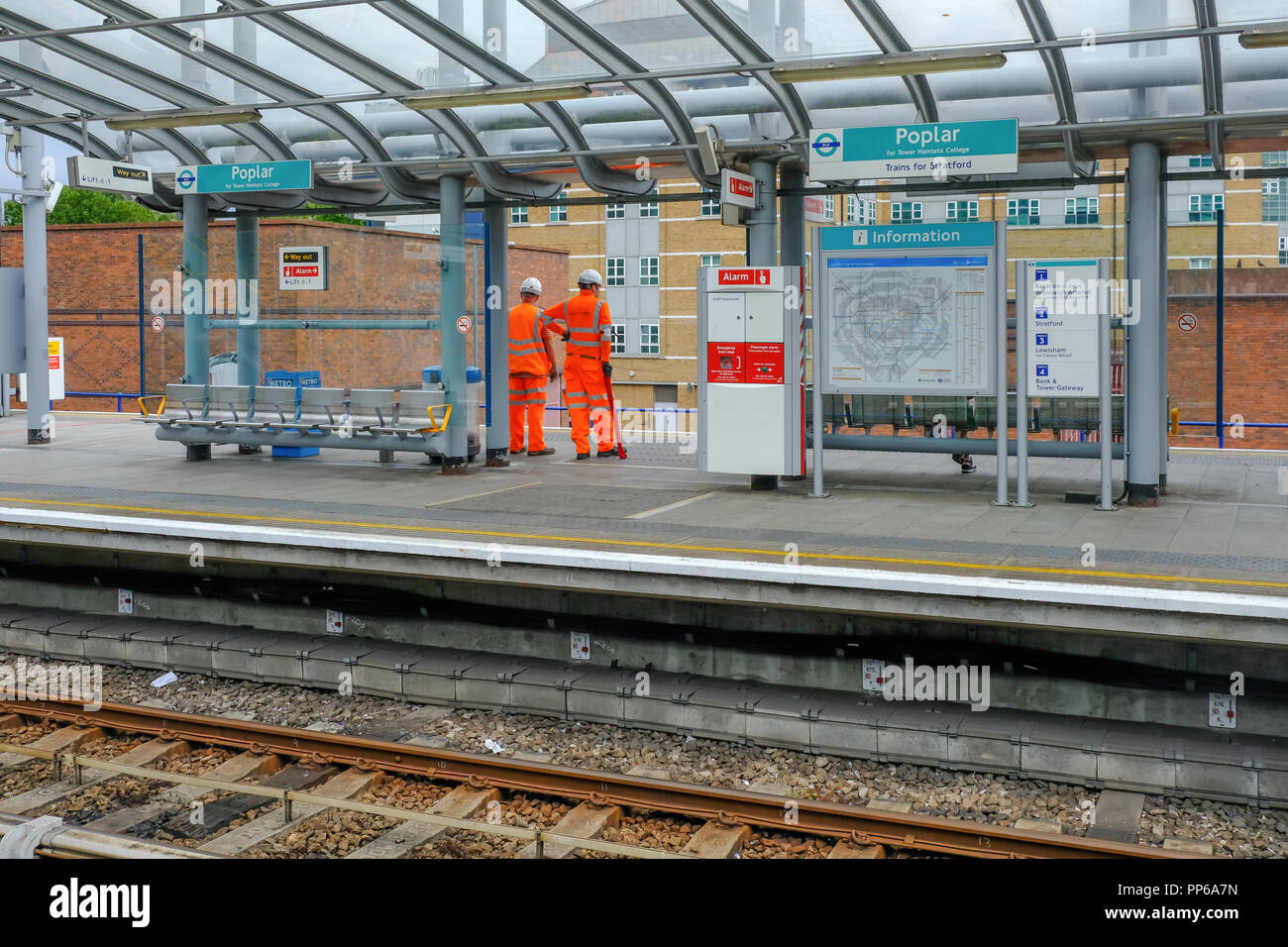 Poplar, London, UK - August 18, 2018: Two workmen dressed in high viz uniform in orange. Shows the workment waiting on the DLR platform for a train. - Stock Image