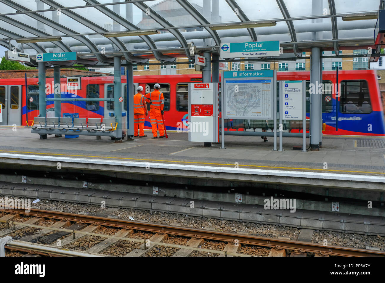 Poplar, London, UK - August 18, 2018: Two workmen dressed in high viz uniform in orange. Shows the workment on the DLR platform as a train pulls in. - Stock Image