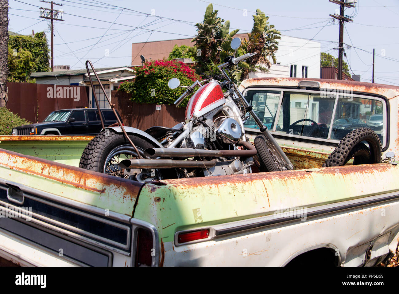 A view of a motorcycle in a vintage pick up truck trunk - Stock Image