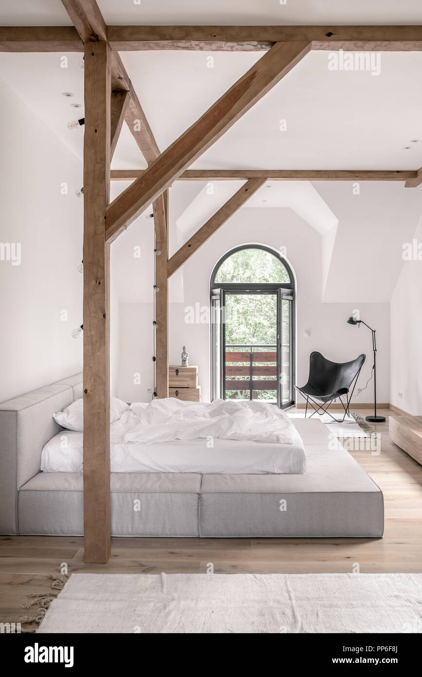 Bedroom in a modern style with white walls, wooden beams and ...