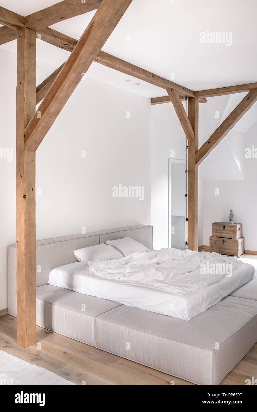 Modern bedroom with white walls, wooden beams and a parquet ...