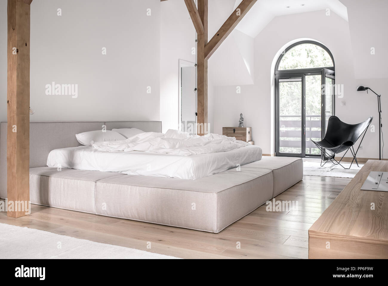 Contemporary bedroom with white walls, wooden beams and a ...