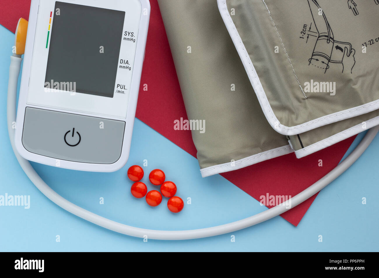 Close-up, a device for measuring blood pressure with tablets on a blue and red background - Stock Image