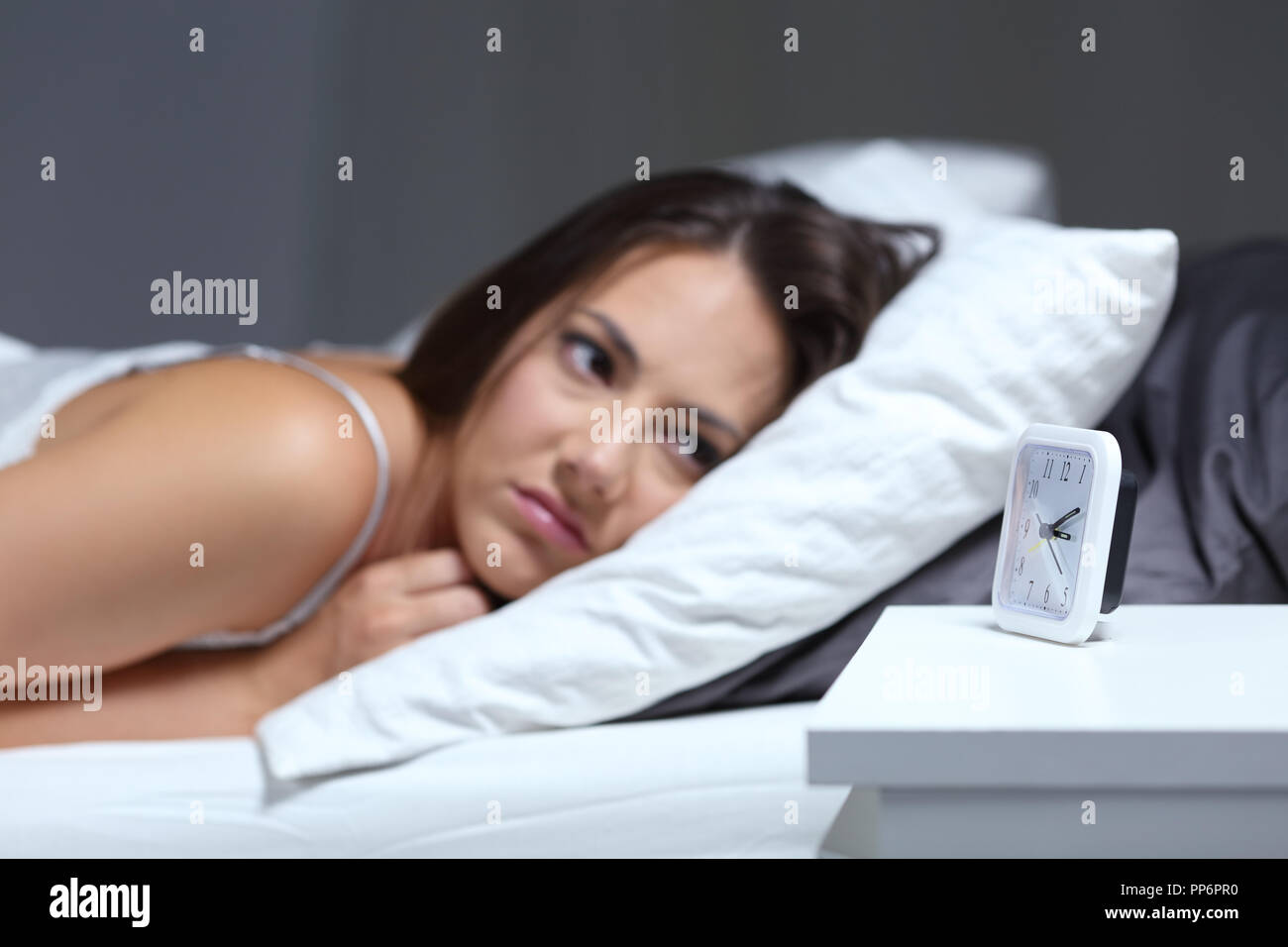 Insomniac woman bored looking at alarm clock in the bed in the night - Stock Image