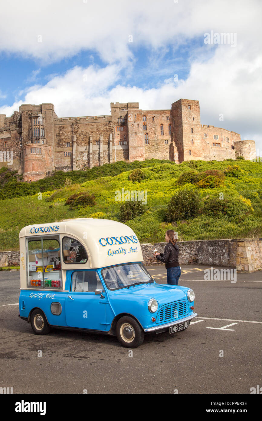 Austin Morris Mini car van converted to an ice cream van parked in front of Bamburgh castle Northumberland England UK - Stock Image