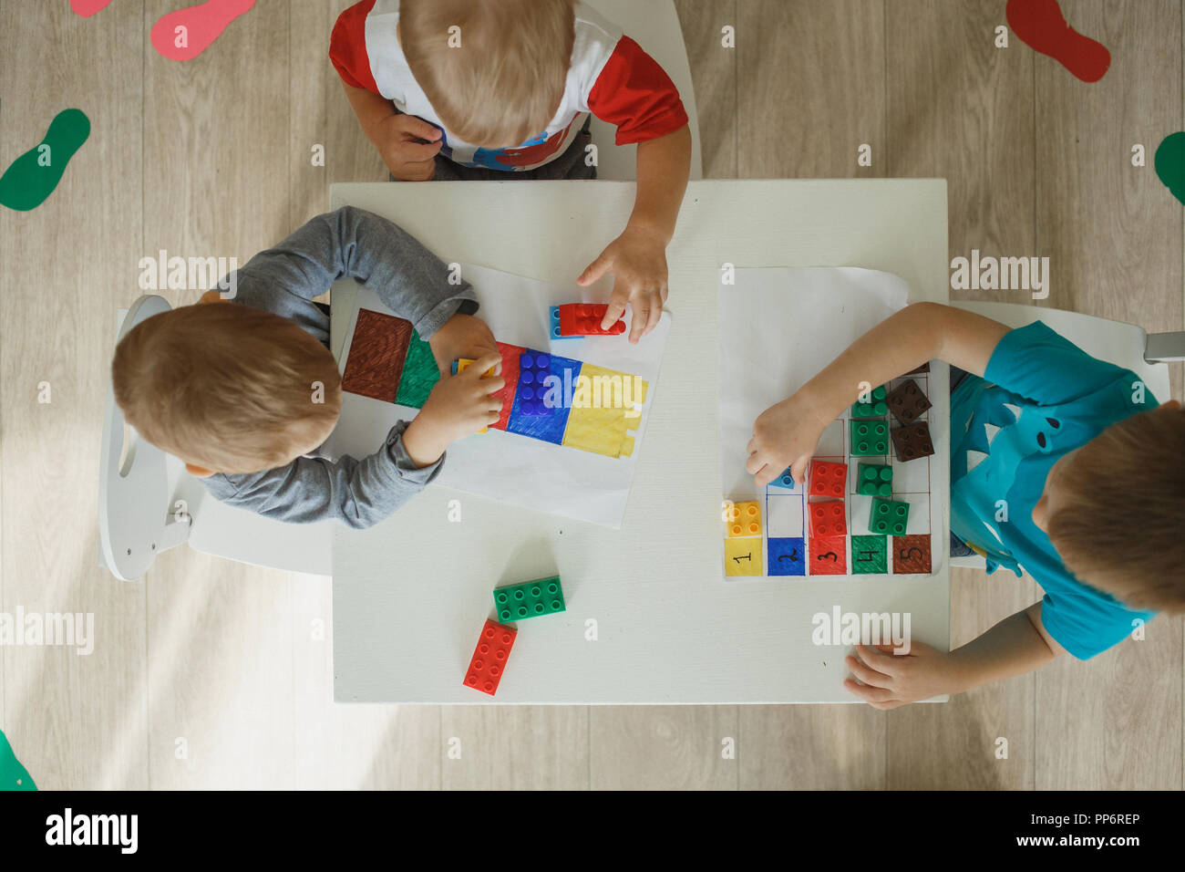 Children playing with blocks educational kit in the kindergarten. Top view picture. - Stock Image