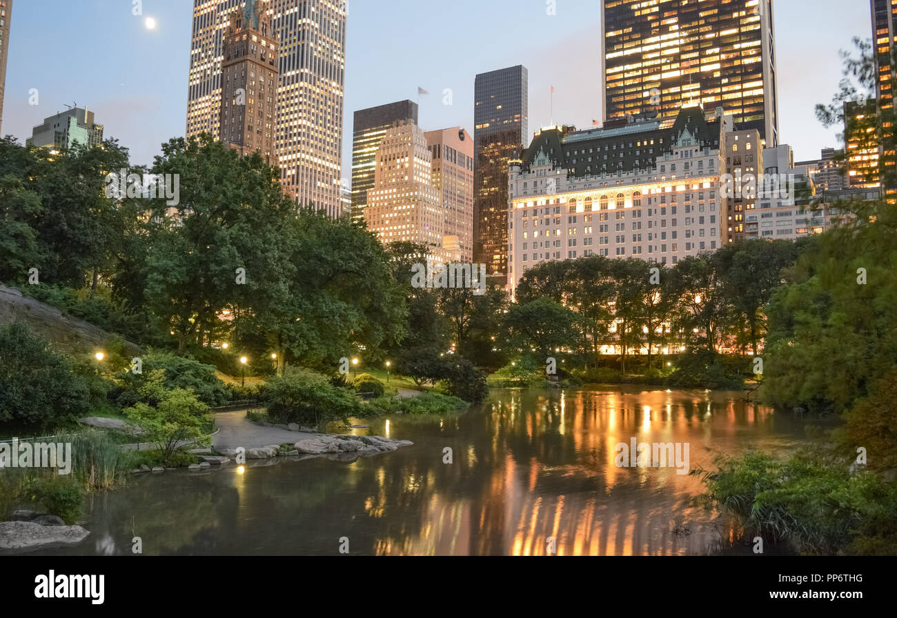The bright lights of the Manhattan skyline are reflected on Central Park's iconic pond on a clear and quiet evening. - Stock Image