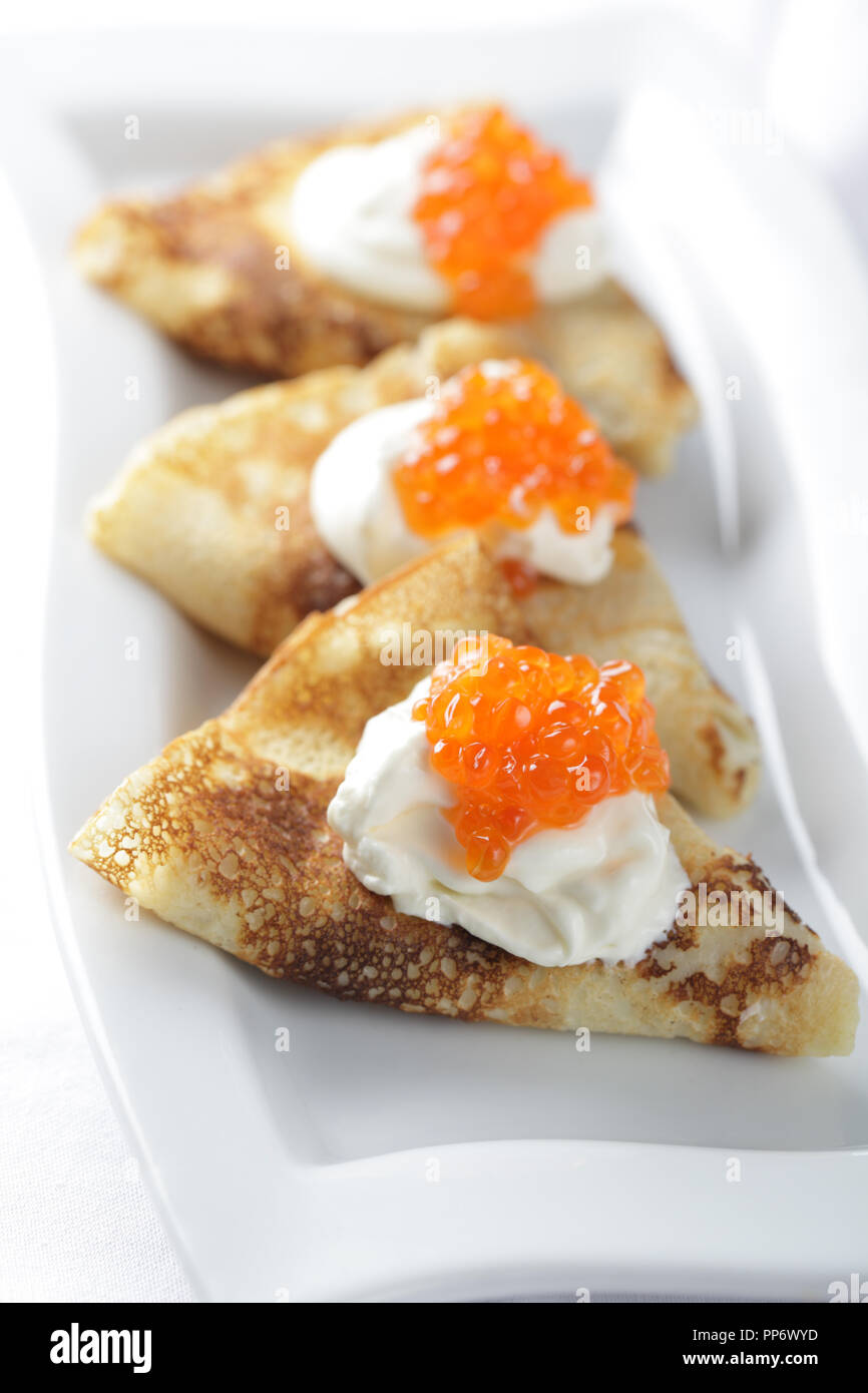 Blinis with sour cream and red caviar - Stock Image
