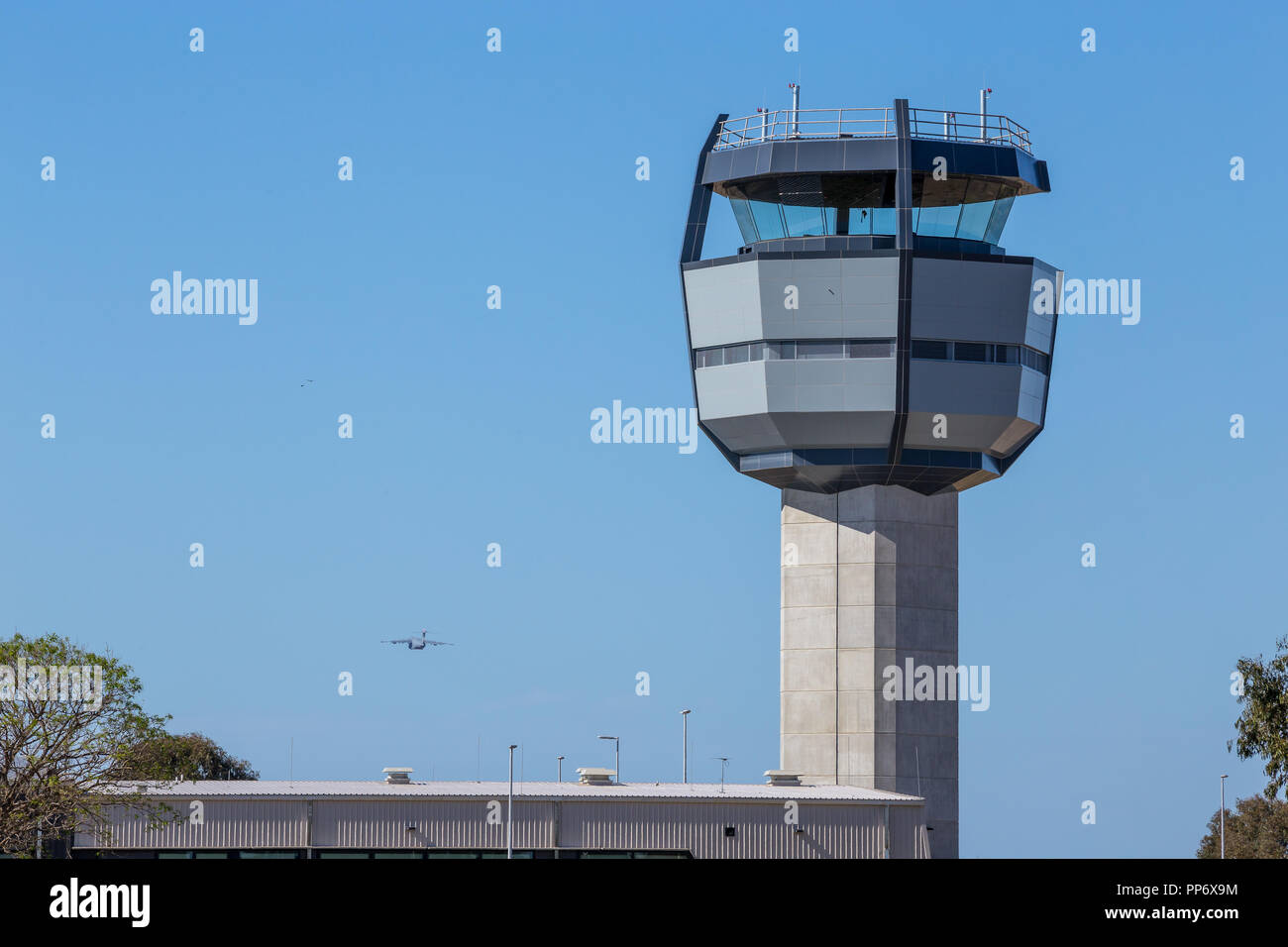 Military Airport, Royal Australian Air Force Base Amberley new control tower, a C17 Globemaster taking off to the left of the tower. - Stock Image
