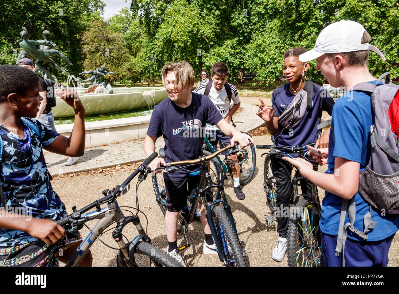 London England United Kingdom Great Britain Hyde Park historic Royal Park Joy of Life Fountain Black boy teen student bicycles cyclists friends - Stock Image