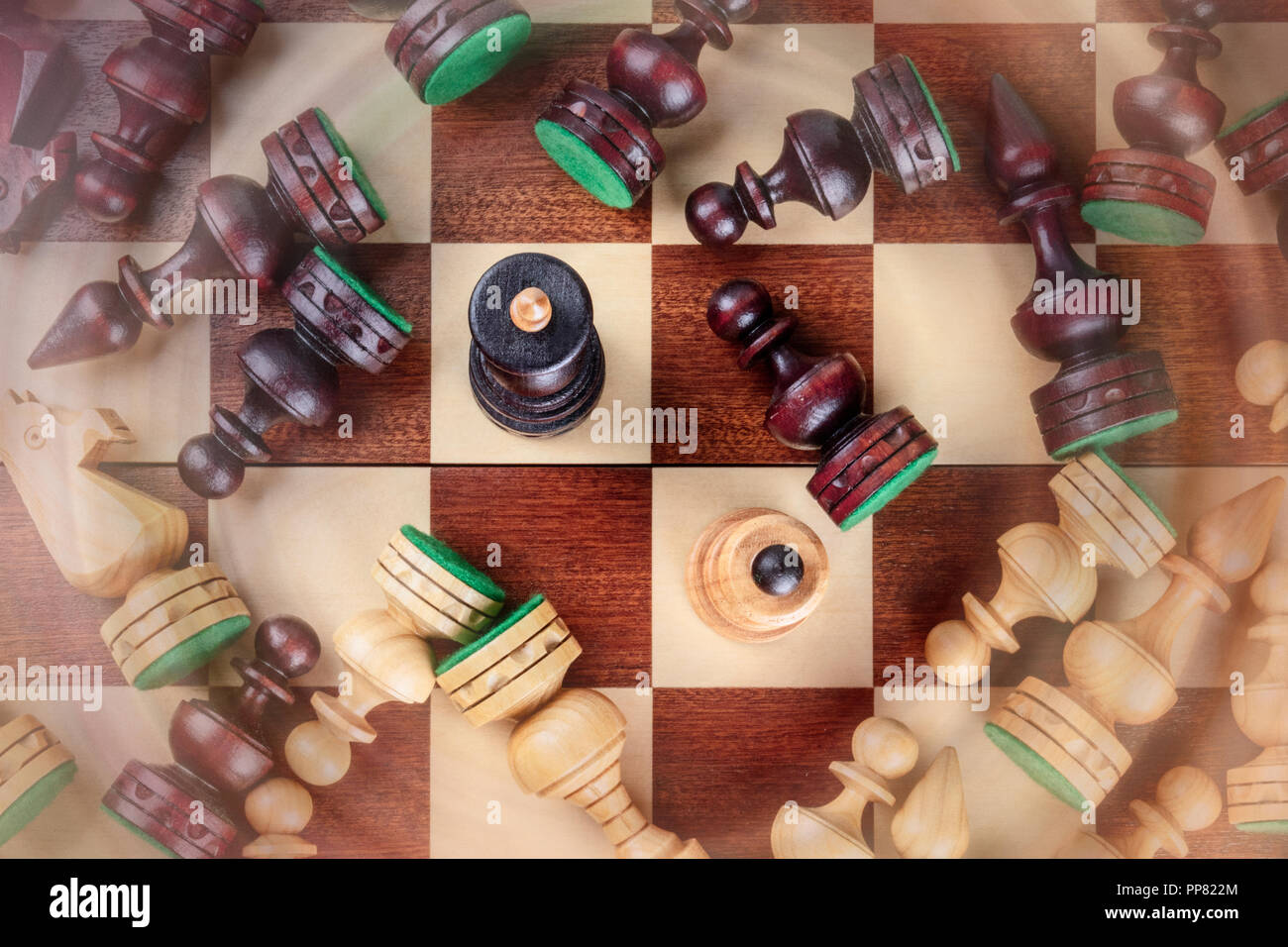 An overhead photo of a checkmate situation in chess with nearly all the pieces fallen on the chessboard, with blurred motion - Stock Image