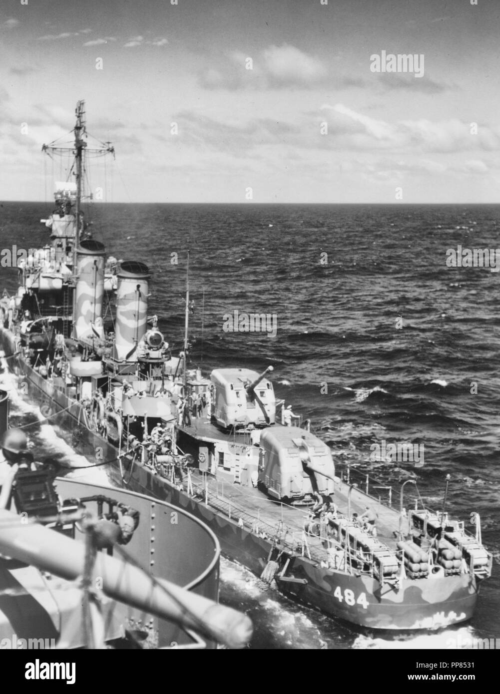USS Buchanan (DD-484) Refueling from USS Wasp (CV-7) while en route to the Guadalcanal-Tulagi invasion area, 3 August 1942. Buchanan is painted in Camouflage Measure 12 (Modified). Note the depth charges in stern racks and on K-Guns, fenders rigged along her sides, and the red refueling flag flying from her foremast. Also note the 5/38 gun aboard Wasp, in the lower left. - Stock Image