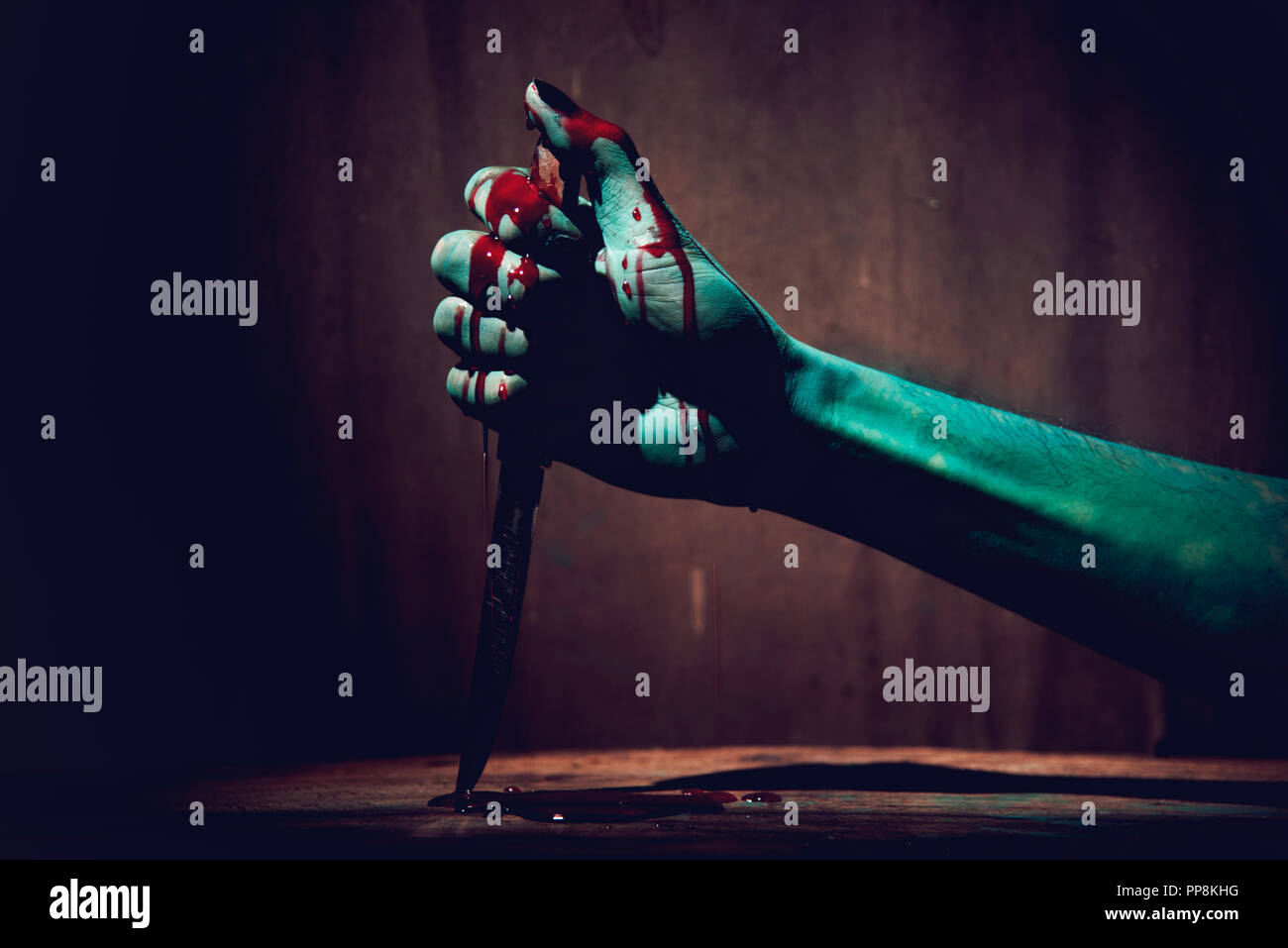 Halloween concept with Bloody stabbing. Hand with knife Stock Photo