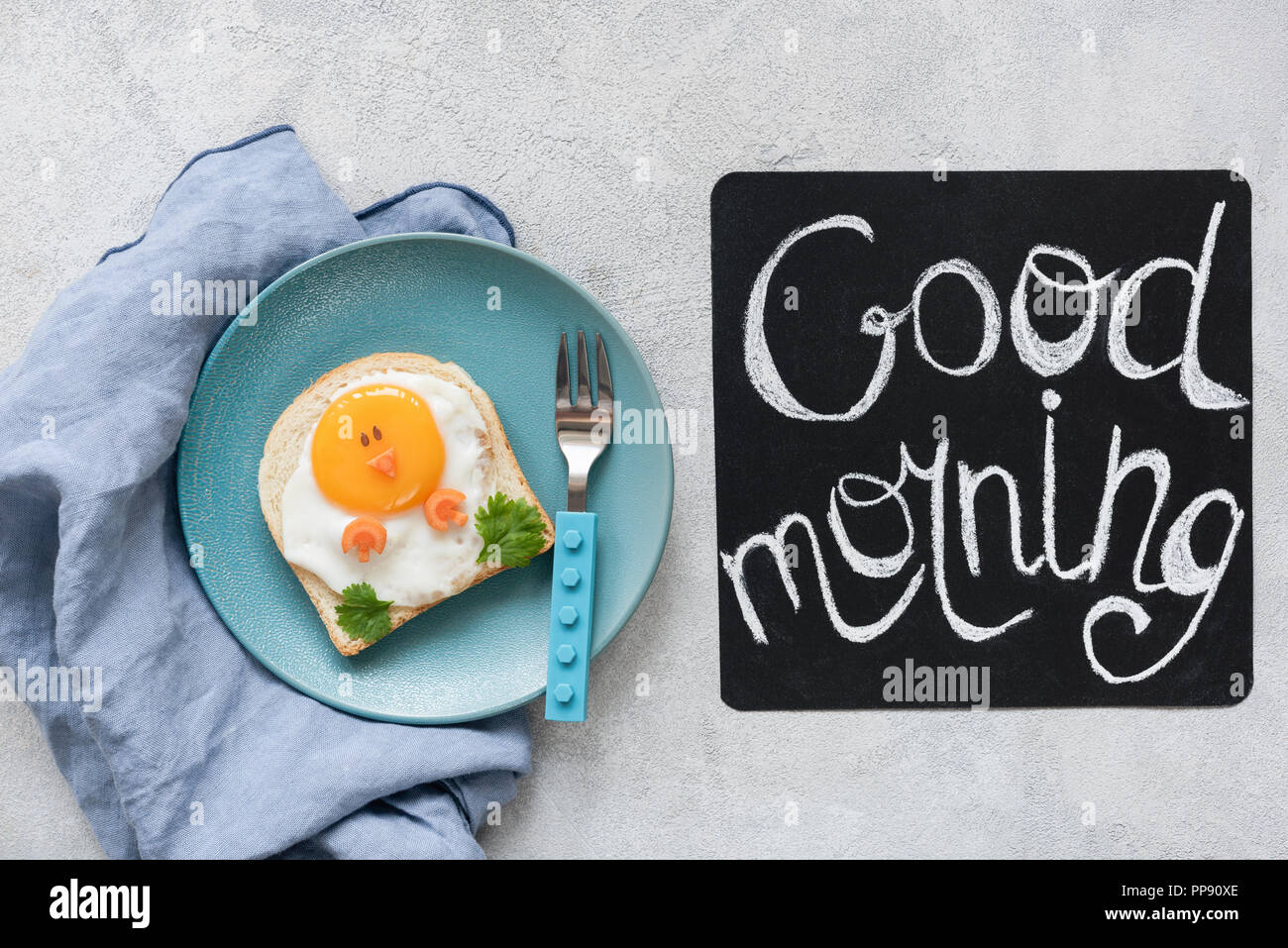 Breakfast food kids. Funny toast with egg and good morning text on a chalkboard. Top view - Stock Image