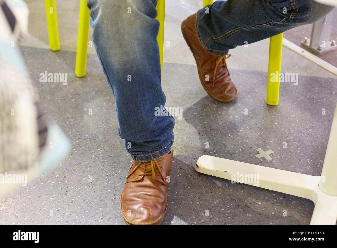 5cd87eecccf men s legs in jeans and brown shoes under a table in a cafe Stock ...
