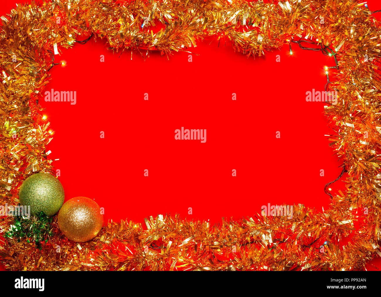 Christmas baubles with lights and tinsel frame on red background - Stock Image