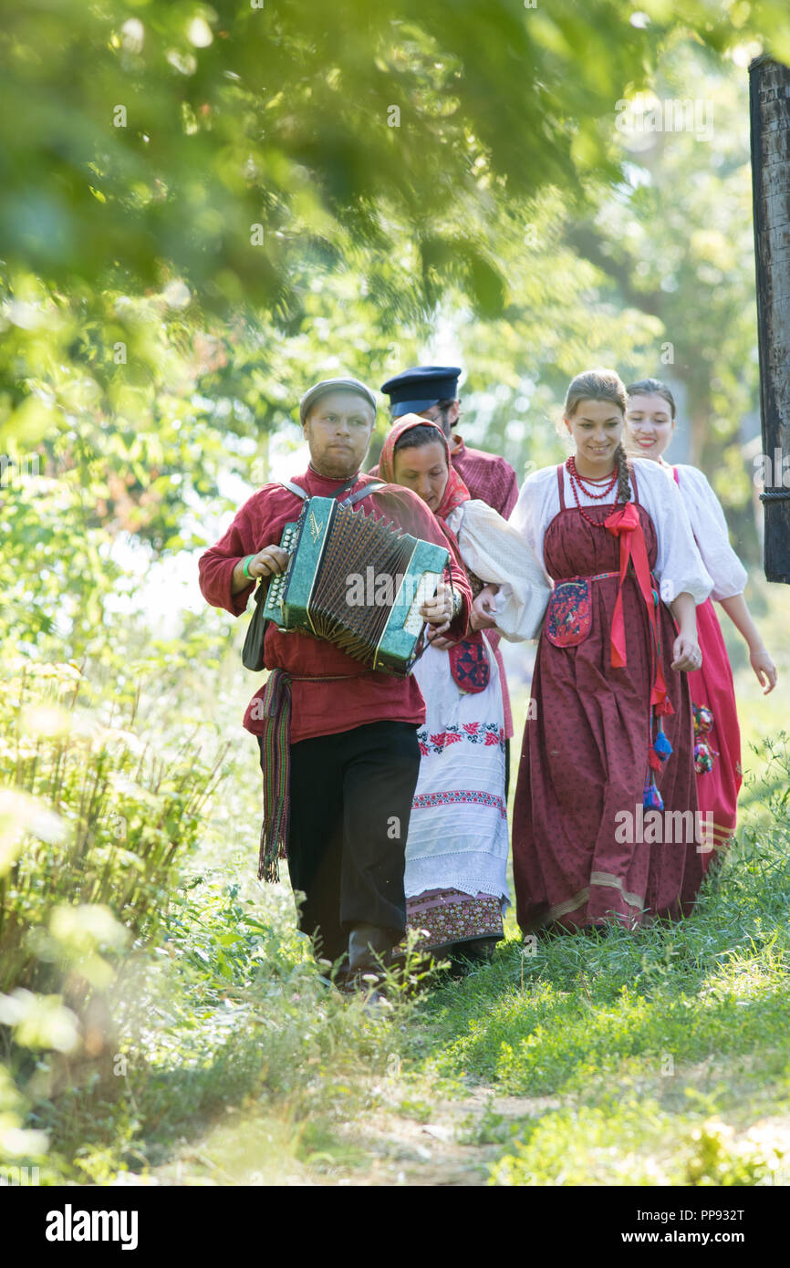 A group of people in Russian folk costumes walking around a