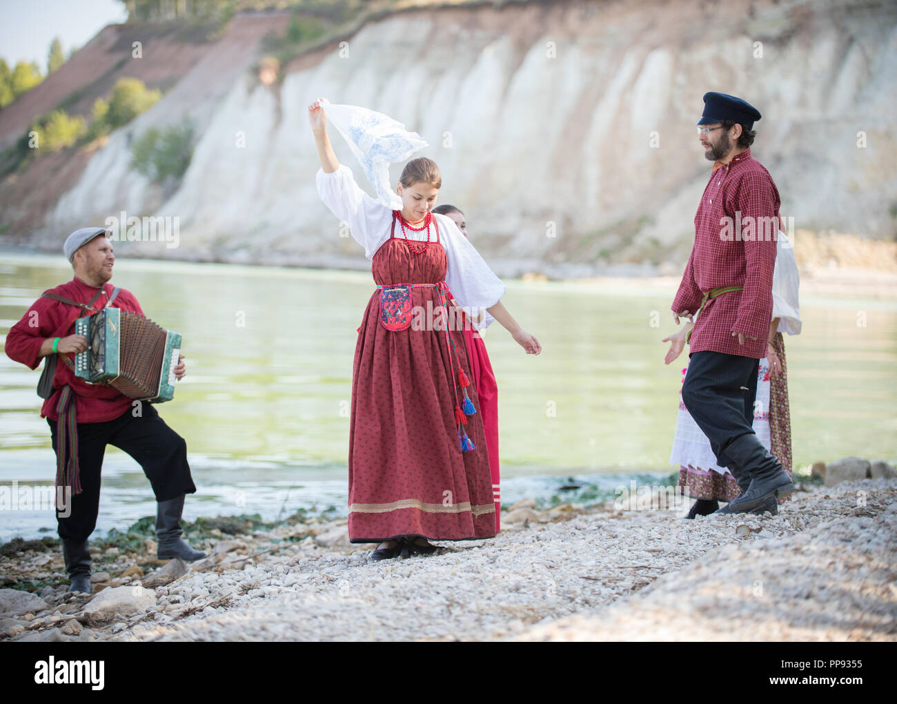 4790bc00 Young people in Russian national costumes dancing, playing accordion -  Stock Image