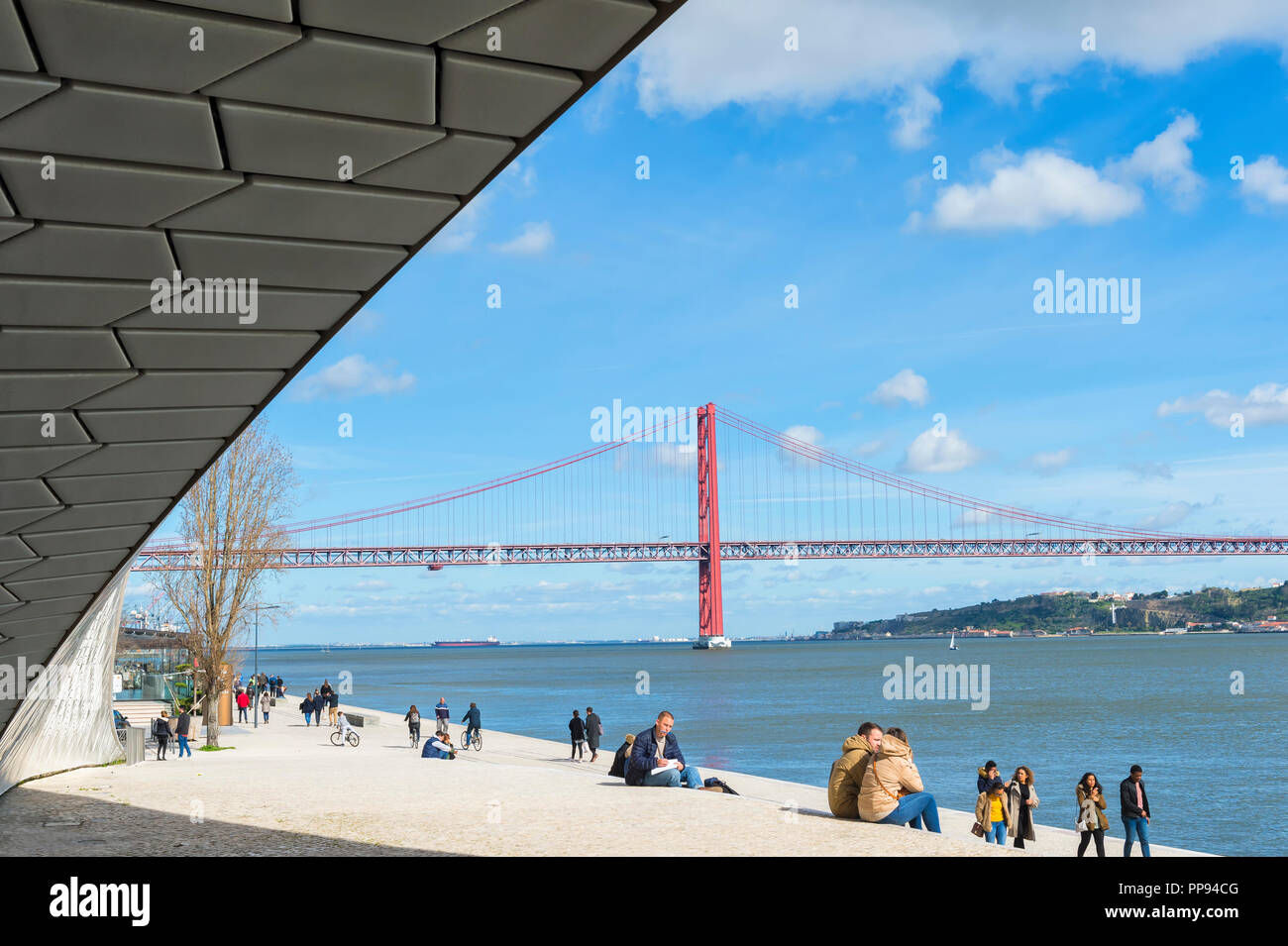 25 April Bridge, former Salazar bridge, over the Tagus river viewed from the MAAT – Museum of Art, Architecture and Technology, Lisbon, Portugal - Stock Image