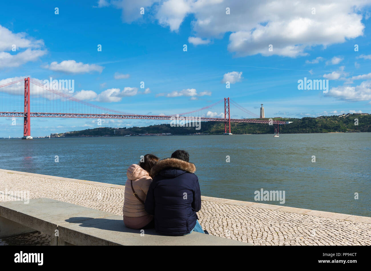 Young Couple seated on the Tagus riverfront and looking at the 25 April Bridge over the Tagus river, Lisbon, Portugal - Stock Image