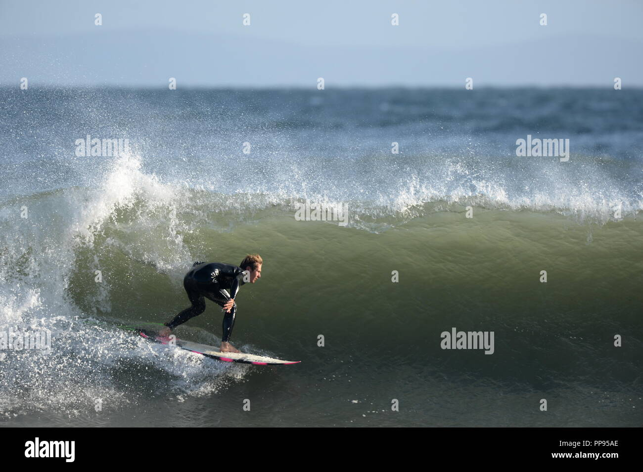 A surfer angles his board down a green wall of water tucking in for a tube - Stock Image