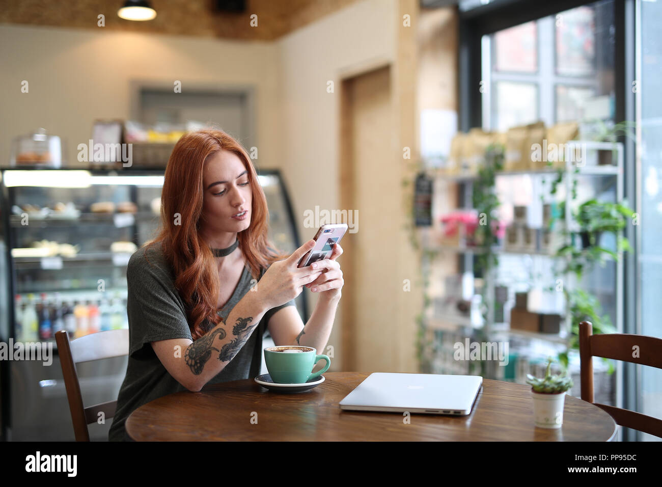 5ed323135 Red Head girl wIth arm Tattoo, sitting alone in a cafe looking at her mobile