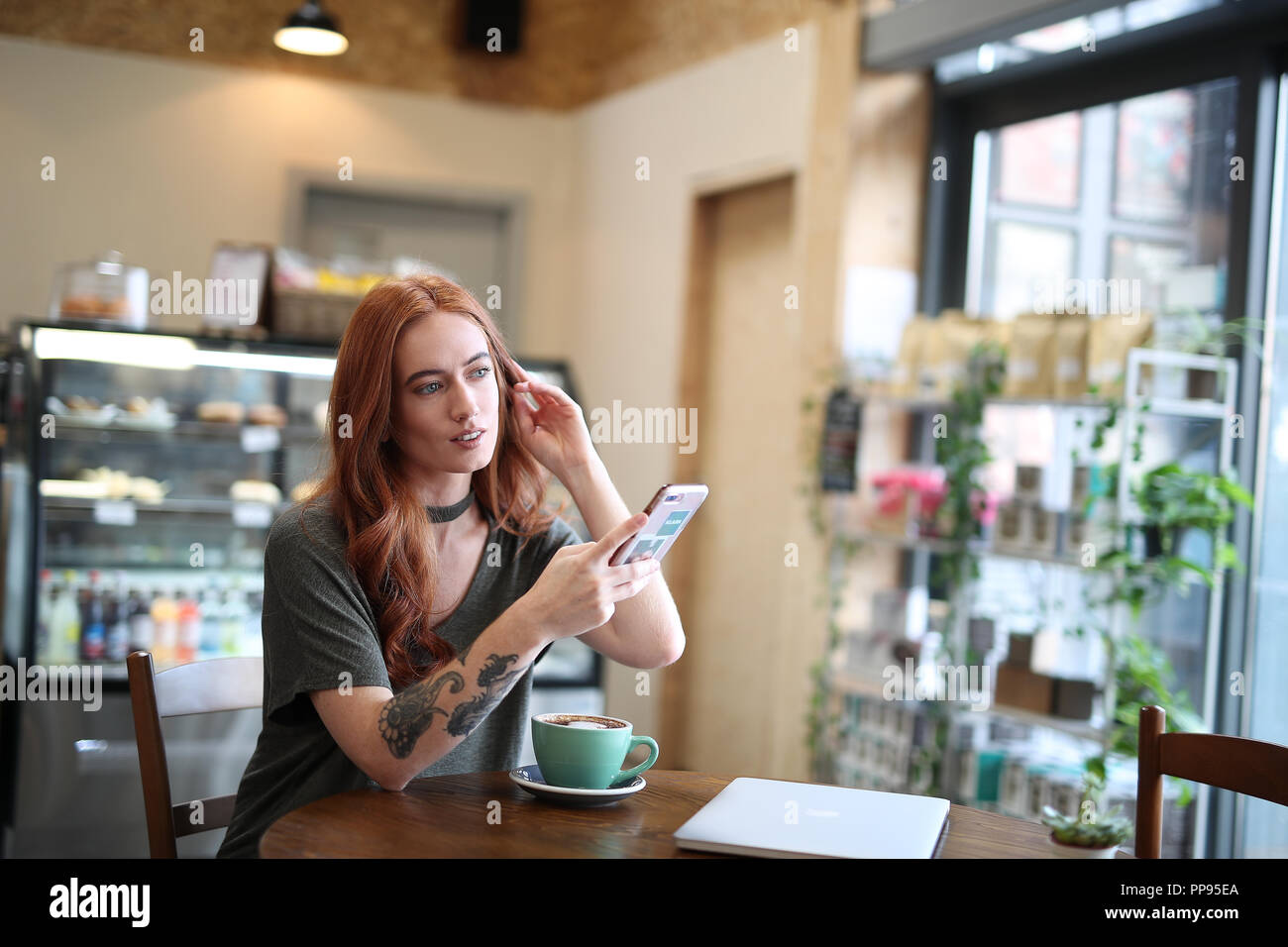 Red Head Girl With Arm Tattoo Sitting Alone In A Cafe Looking At