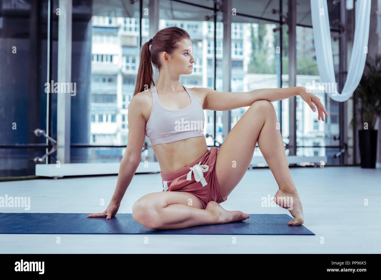 Earnest sportive woman training her acrobatic skills - Stock Image