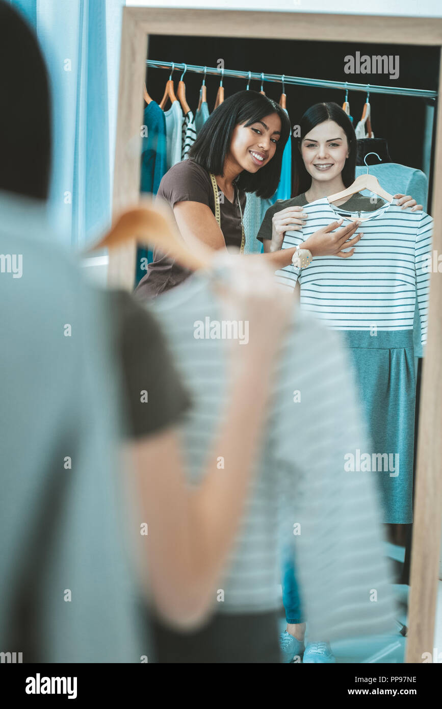 Positive delighted brunettes standing before mirror - Stock Image