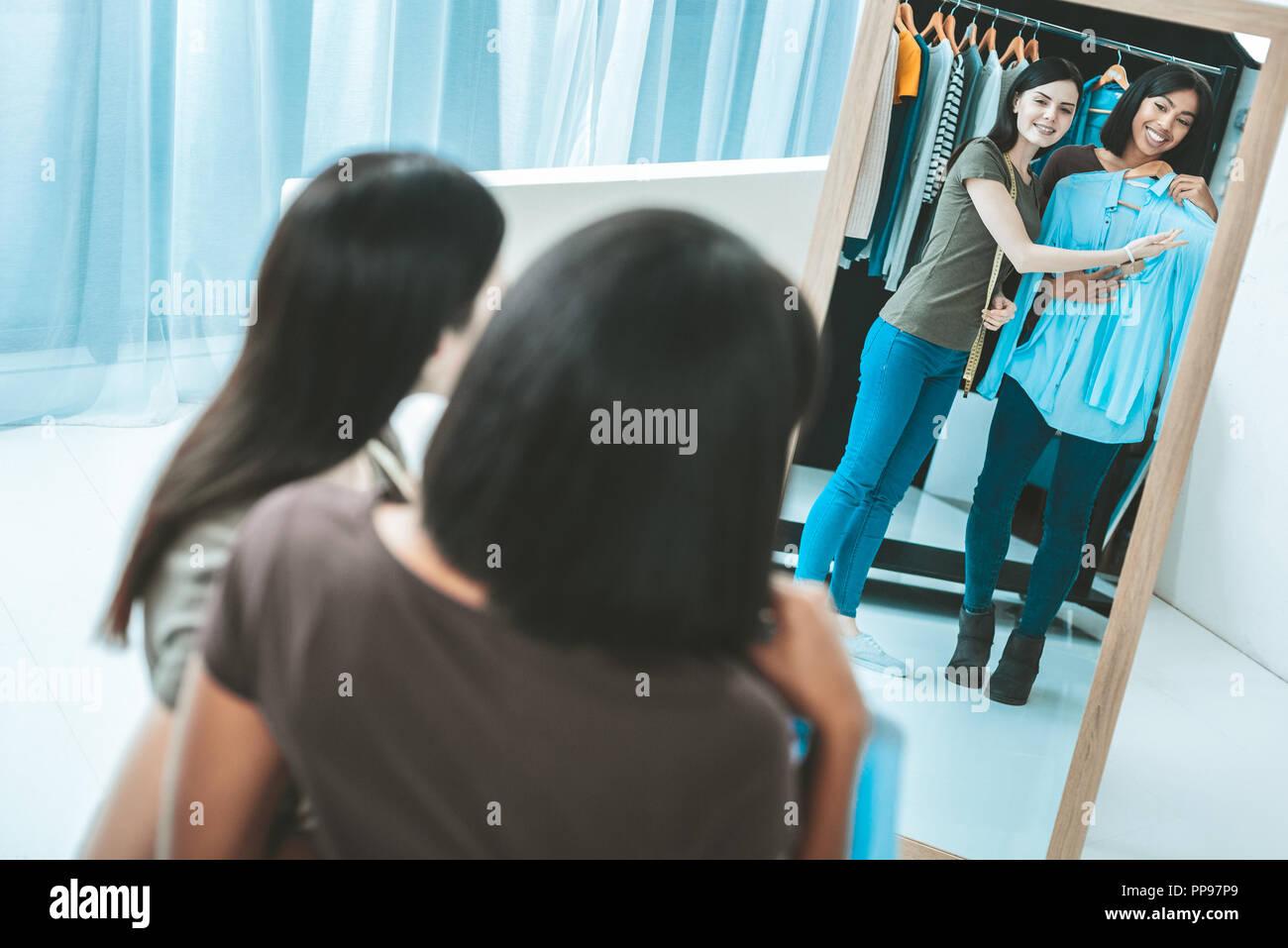 Happy brunettes wearing blue blouse - Stock Image