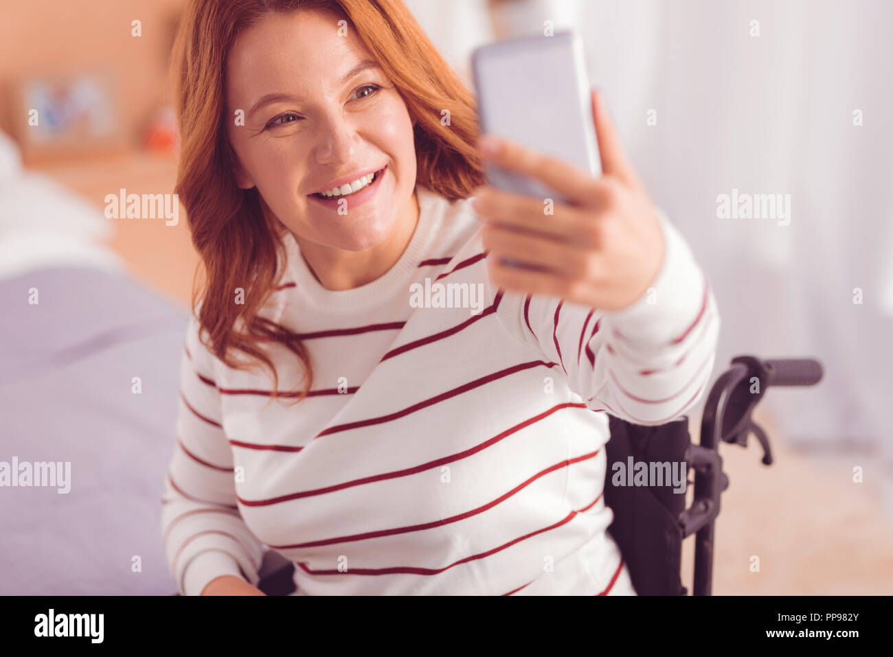 Joyful wheelchaired woman making selfies - Stock Image