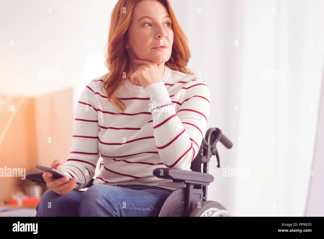 Serious disabled woman sitting in the wheelchair - Stock Image
