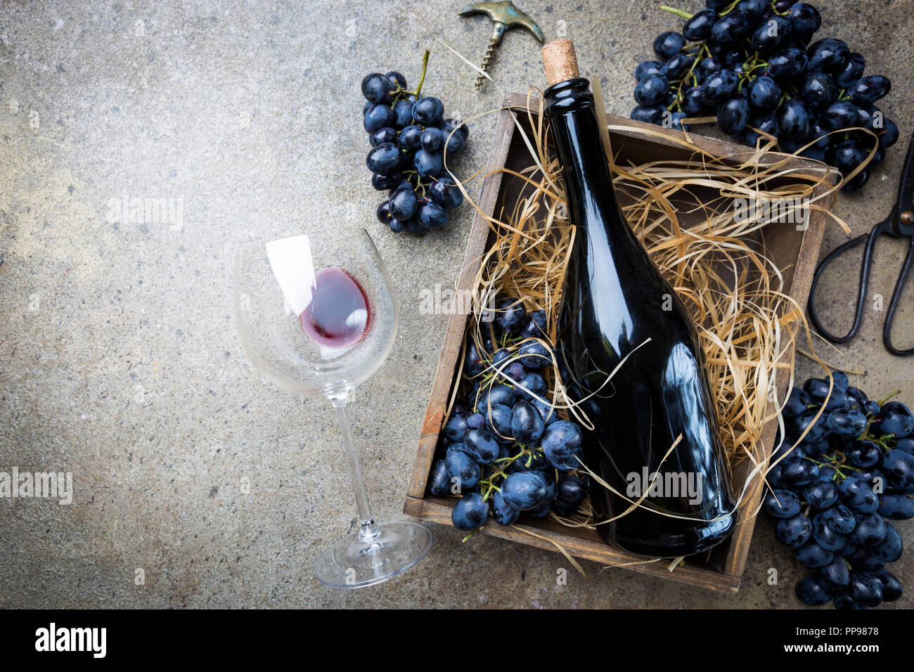 A bottle of red wine in a box with grapes on a gray stone background, copy space , top view. Stock Photo