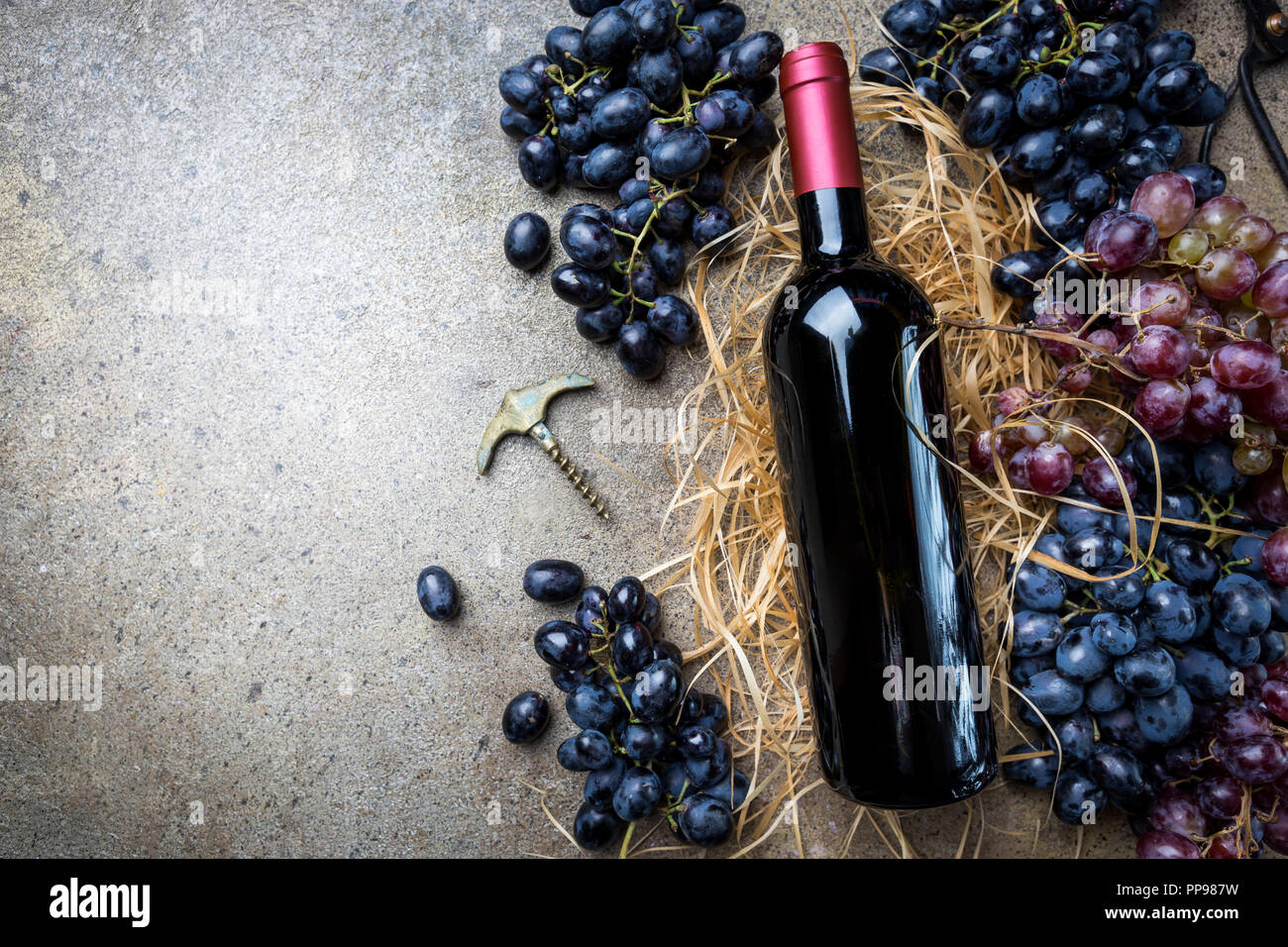 A bottle of red wine with grapes on a gray stone background, copy space , top view. Stock Photo