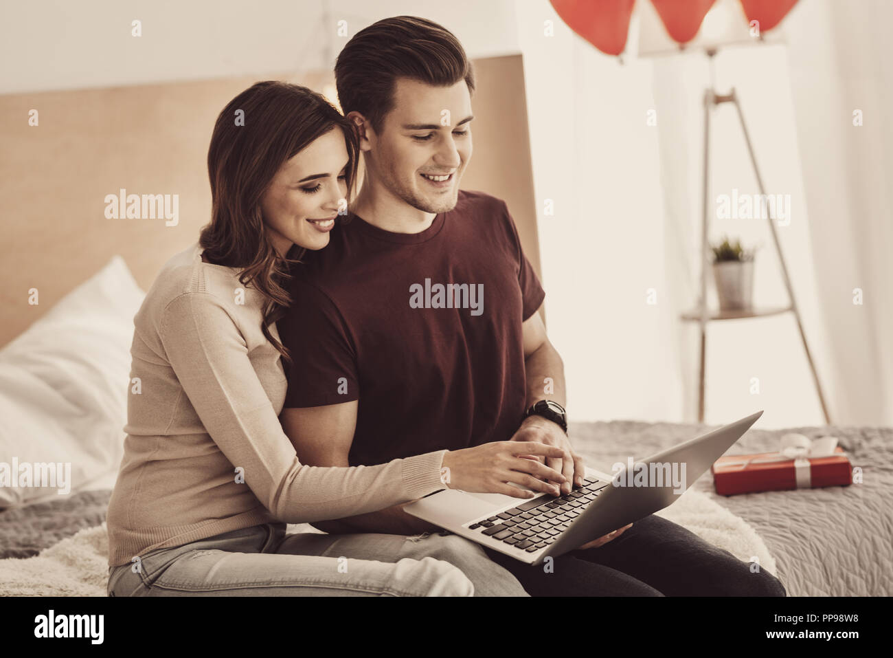 Skillful businesswoman helping boyfriend typing business letter on laptop - Stock Image